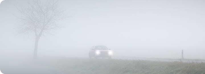 Auto rijdt door de mist