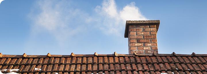 Rookpluim uit schoorsteen op dak
