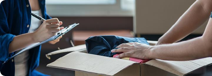 Twee personen pakken een verhuisdoos in aan de hand van een checklist